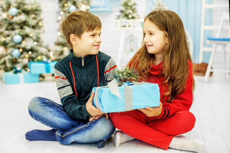 Merry children give presents. The boy and the girl. Happy Christ royalty free stock image