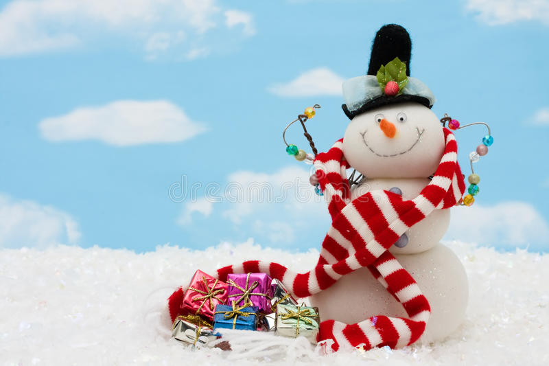 Merry Christmas. Snowman wearing scarf on blue sky background, merry Christmas stock photo