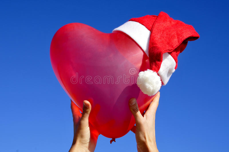 Merry christmas. A heart-shaped balloon with a santa hat royalty free stock photos