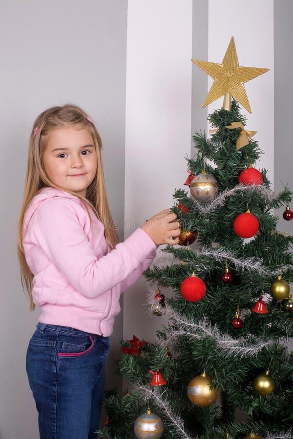 Merry Christmas. Little girl decorating Christmas tree royalty free stock photo