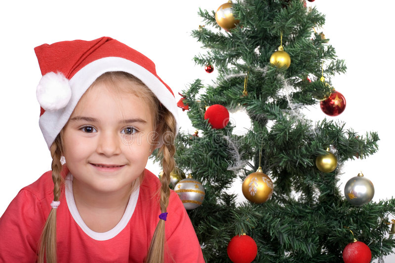 Merry Christmas. Cute Santa girl in front of a Christmas tree royalty free stock photography