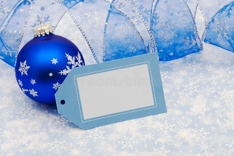 Merry Christmas. Blank gift tag with blue ribbon and glass ball on blue snowflake background, merry Christmas stock images