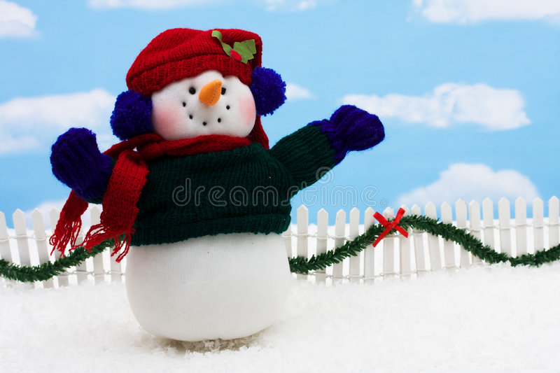 Merry Christmas. Snowman and white picket fence with green garland and red bow, merry Christmas royalty free stock photos
