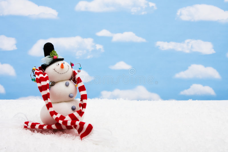 Merry Christmas. Snowman wearing scarf on sky background, merry Christmas stock photo