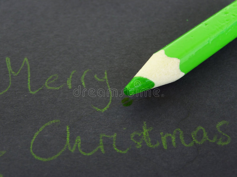 Merry Christmas. Childlike handwriting, green pencil and Merry Christmas written on dark blackground Suitable for Christmas cards, greetings, etc. *RAW format royalty free stock image