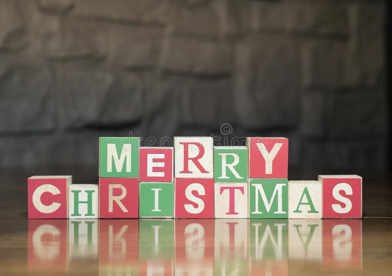 Merry Christmas against a Rock Wall. Wood blocks in green, red and light wood with capital letters spelling Merry Christmas. Photographed with a shallow depth of royalty free stock photography