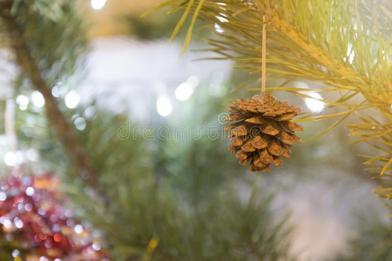 Merry Christmas background. Cone on decorated pine tree closeup over blurred garland lights shinig stock photo