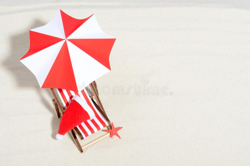 Merry Christmas on beach concept. Lounge chair with umbrella and Santa hat. Top view i royalty free stock image
