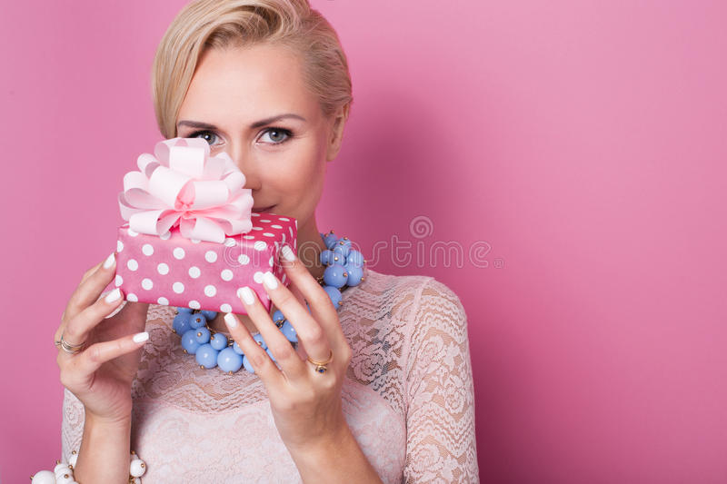 Merry christmas. Beautiful blonde woman holding small gift box with ribbon. Soft colors stock photo