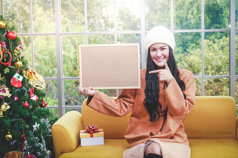 Merry Christmas. A beautiful woman with a brown board has space to write a message. stock images