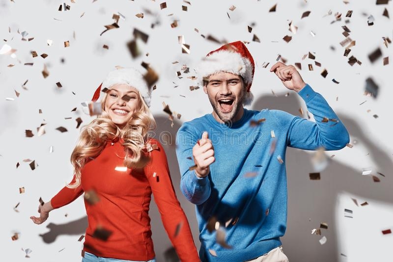 Merry Christmas!. Beautiful young couple in Christmas hats gesturing and smiling while standing against grey background stock photos