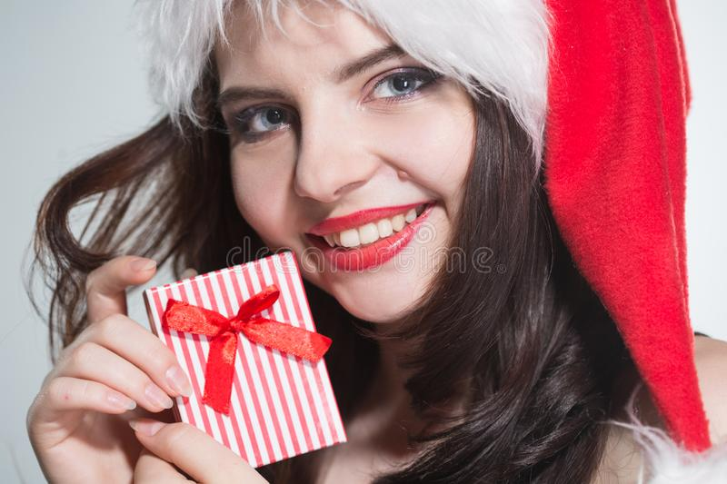 Merry Christmas. Beautiful young woman in a red Mrs. Claus costume and Santa cap holding gift box stock images
