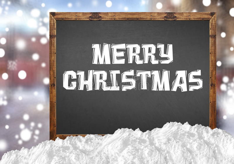Merry Christmas on blank blackboard with blurr city and snow. Close stock photos