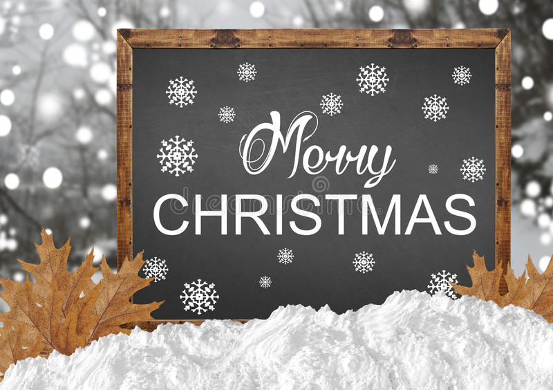 Merry Christmas on blank blackboard with blurr forest leaves and. Snow close royalty free stock image