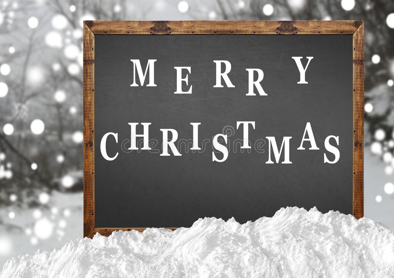Merry Christmas on blank blackboard with blurr forest and snow. Close stock images
