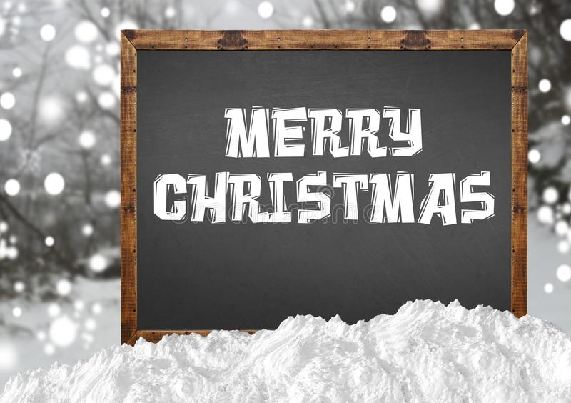 Merry Christmas on blank blackboard with blurr forest and snow. Close stock photo