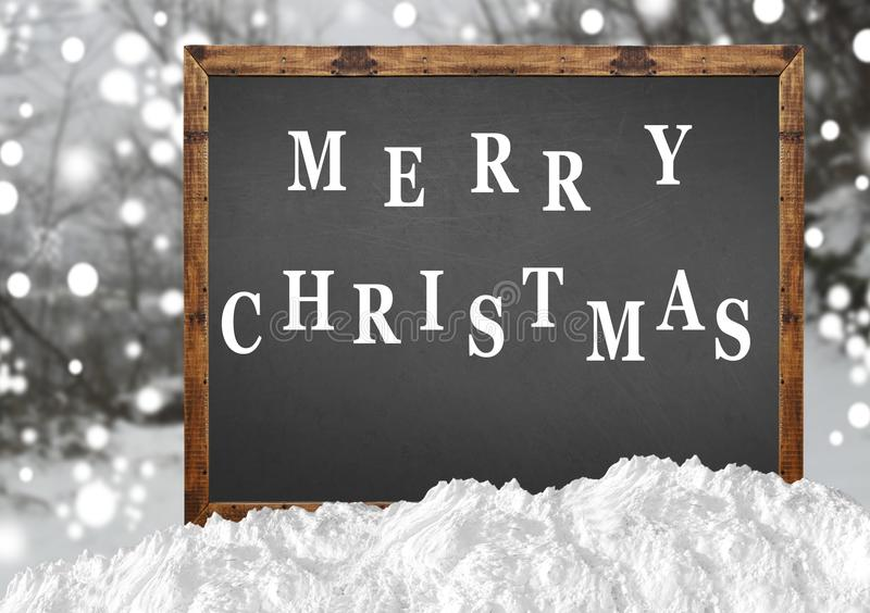 Merry Christmas on blank blackboard with blurr forest and snow. Close royalty free stock photo