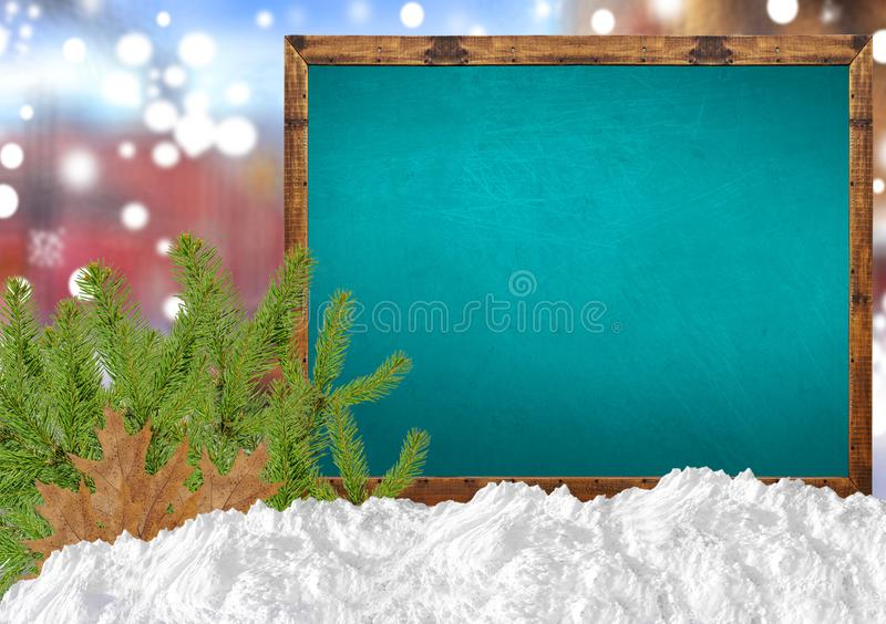 Merry Christmas on blank blue blackboard with blurr city pine. Close royalty free stock photography