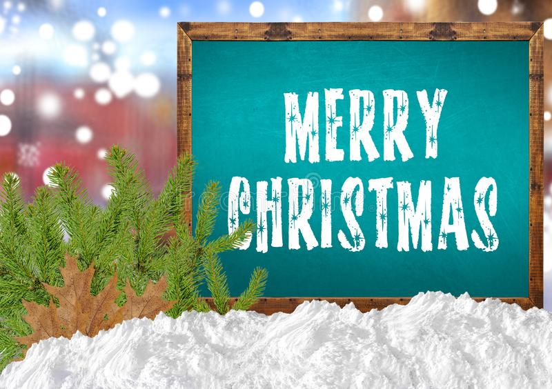 Merry Christmas on blue blackboard with blurr city pine and snow. Close royalty free stock image