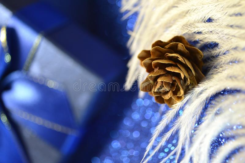 Merry christmas blue gift box with ribbon bow on bokeh lights background with white feather and cone. In the foreground. Winter holiday macro shot cozy concept royalty free stock photo