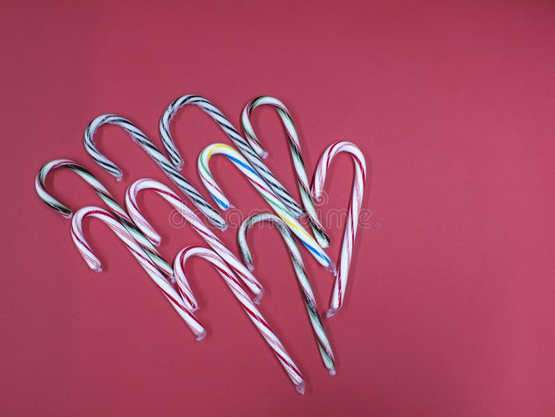 Merry Christmas candy caramel cane on a pink background.  stock image