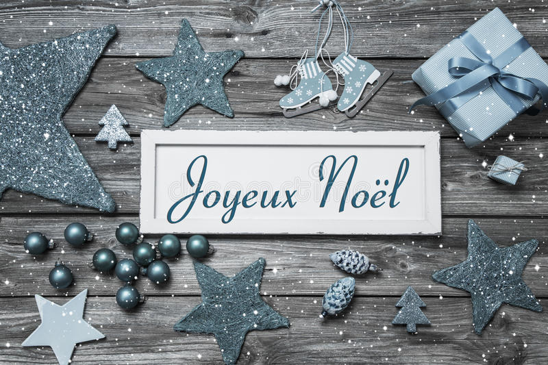 Merry Christmas card in blue and white with french text on wooden board. stock image