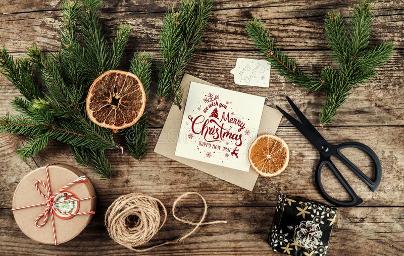 Merry Christmas card with fir branches, gifts on wooden background with scissors and skein of jute. Xmas and Happy New Year theme,. Snow. Flat lay, top view stock images