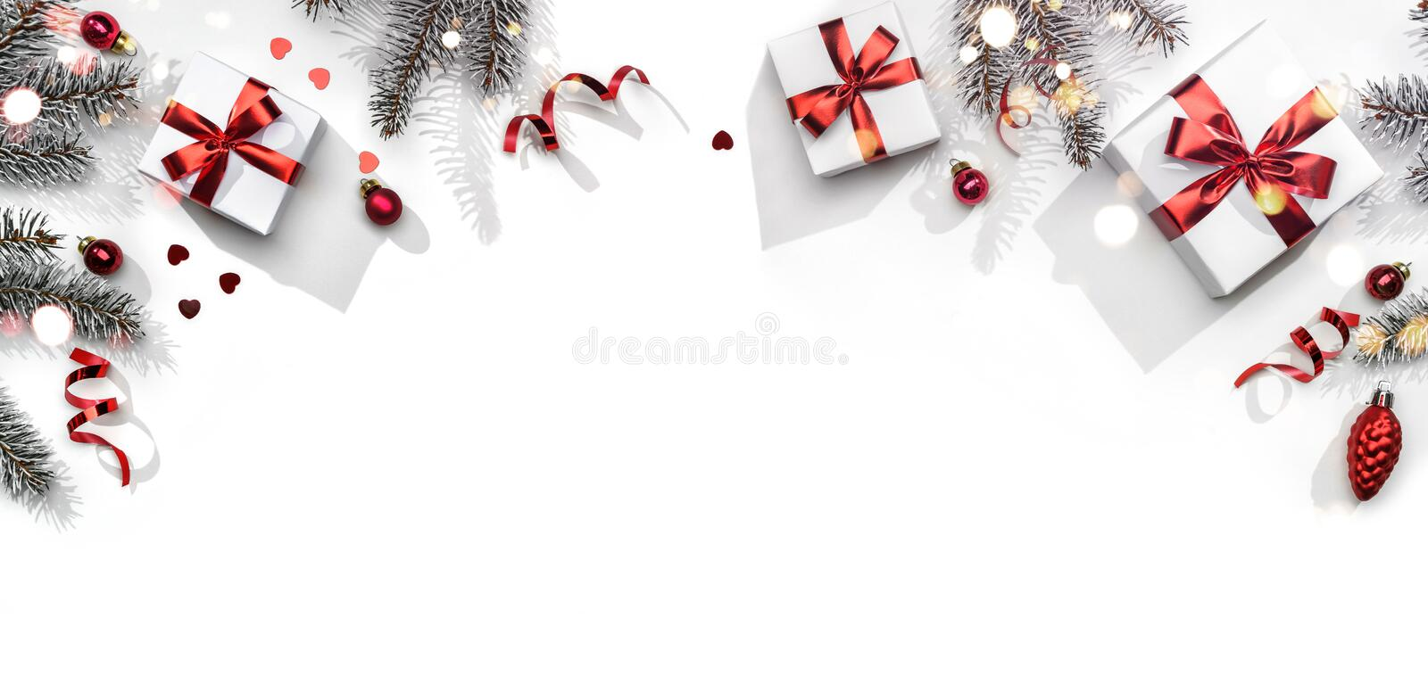 Merry Christmas card made of fir branches, gift boxes, red decoration, sparkles and confetti on white background. Xmas and New stock photo