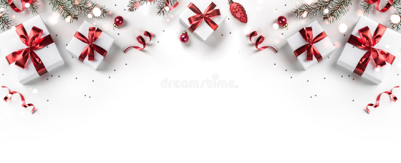 Merry Christmas card made of fir branches, gift boxes, red decoration, sparkles and confetti on white background. Xmas stock image