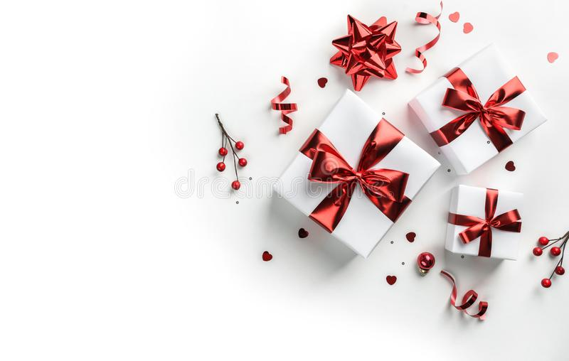 Merry Christmas card made of gift boxes, red decoration, sparkles and confetti on white background. Xmas and New Year holiday, royalty free stock photos