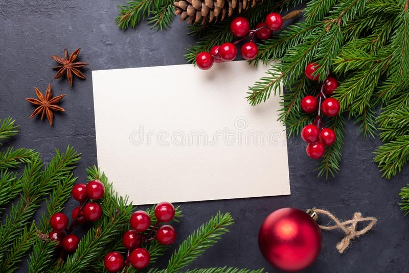 Merry Christmas card with paper, gift box, holly berries and fir tree branch on stone background. Top view royalty free stock images