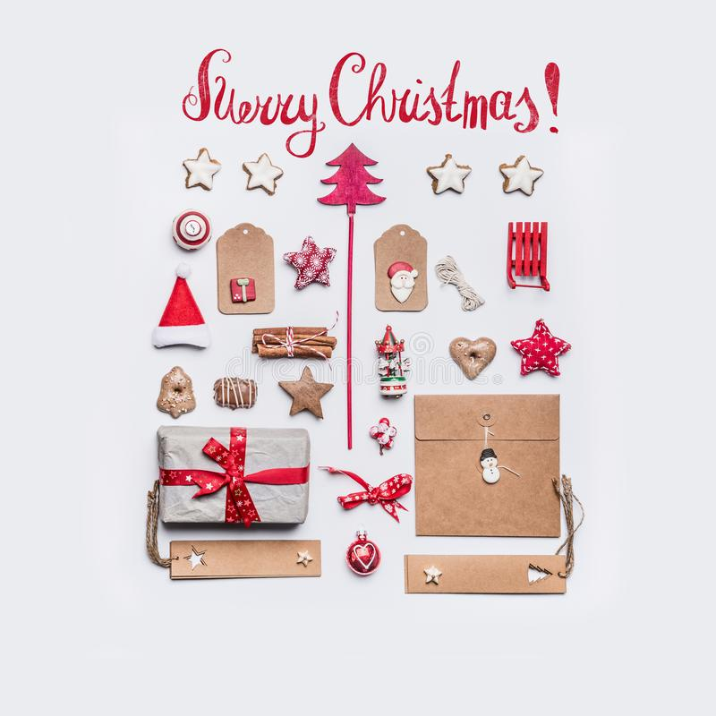 Merry Christmas card with text lettering, holiday gift, craft paper, ribbon , vintage toys, tags, cookies and gingerbread on white royalty free stock photos