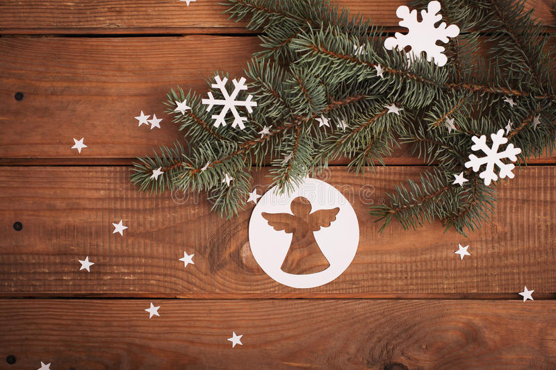 Merry Christmas cards decorations in paper cutting with fir. Merry Christmas cards decorations in paper cutting style hanging on fir over wooden royalty free stock photos