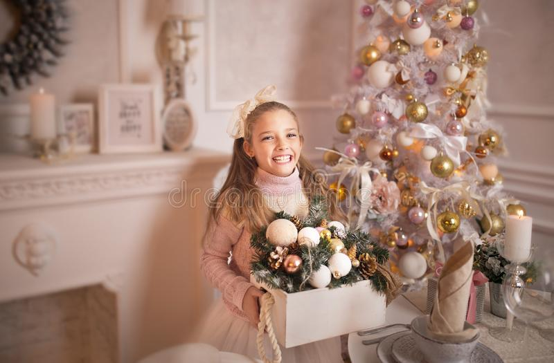 Merry Christmas celebration. Beautiful little girl in a dress lying near the Christmas tree. Winter holidays. Happy New Year royalty free stock photos