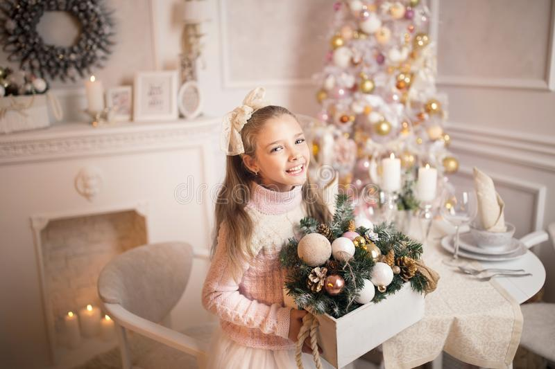 Merry Christmas celebration. Beautiful little girl in a dress lying near the Christmas tree. Winter holidays. Happy New Year royalty free stock photo