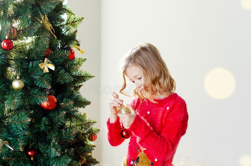 Merry Christmas and happy holidays! Cute little child girl with xmas present. Merry Christmas! Children play near the Christmas tree. Give for New Year`s gifts stock image