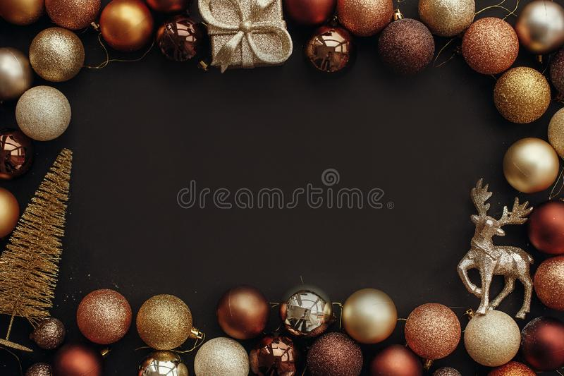 Merry Christmas. Christmas gold frame of gift box, tree, reindeer and glitter baubles on stylish black background. Christmas flat. Lay with space for text stock photo