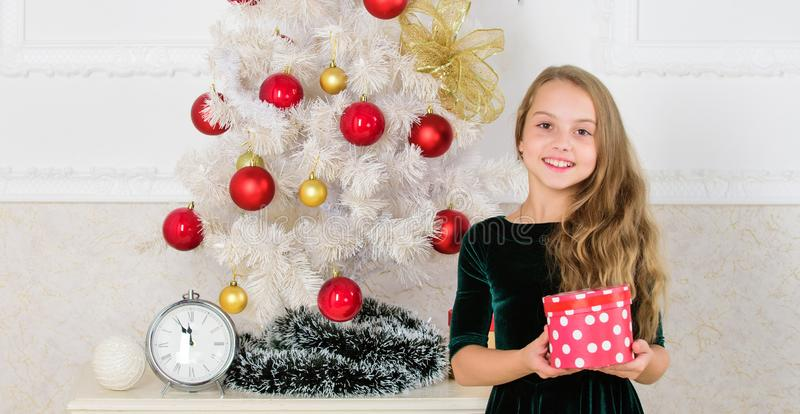 Merry christmas concept. Dreams come true. Best for our kids. Child celebrate christmas at home. Favorite day of the. Year. Kid girl near christmas tree hold stock photography