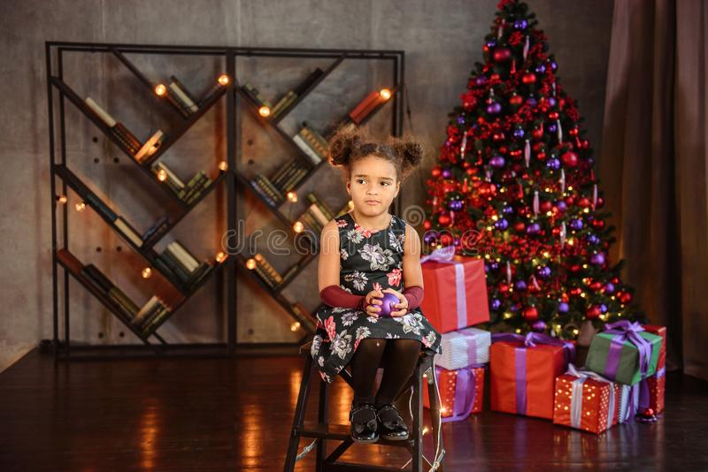 Merry Christmas! Cute little child girl is decorating the Christmas tree royalty free stock image