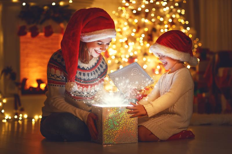 Merry Christmas! family mother and child with magic gift at ho. Me near Christmas tree and fireplace stock photo