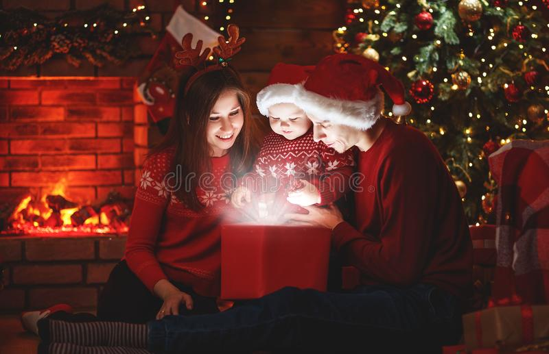 Merry Christmas! family mother father and baby with a magic gift. At Christmas tree stock photography