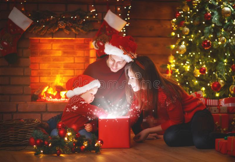 Merry Christmas! family mother father and baby with a magic gift. At Christmas tree stock photos