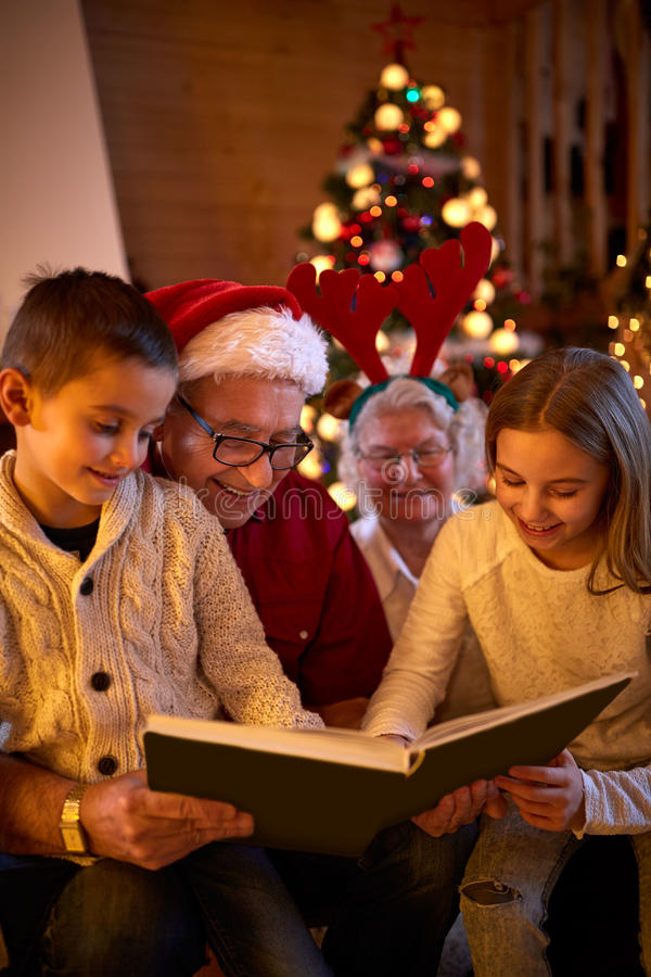 Merry Christmas - family reading book. Merry Christmas concept - family reading book stock photos