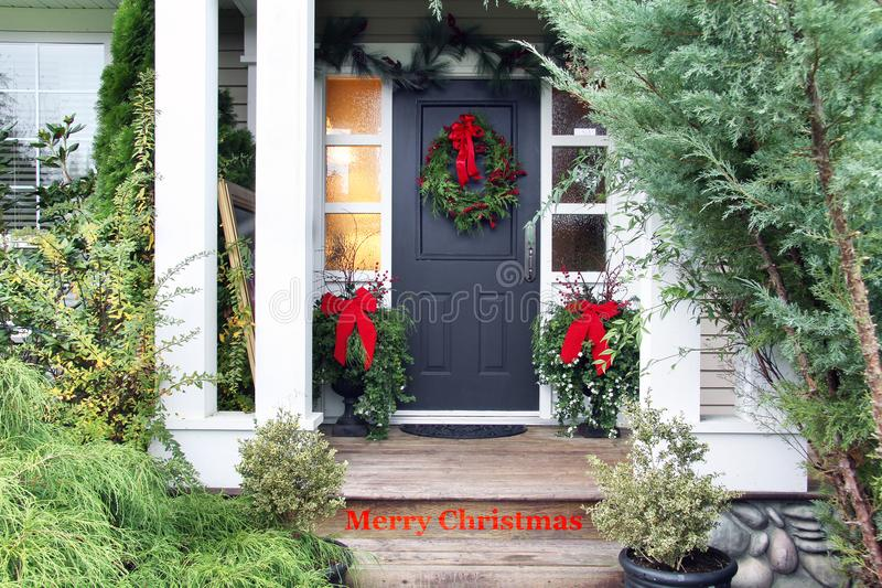 Merry Christmas front door. Front door with a Christmas wreath and bows. Merry Christmas stencilled on the front step stock image