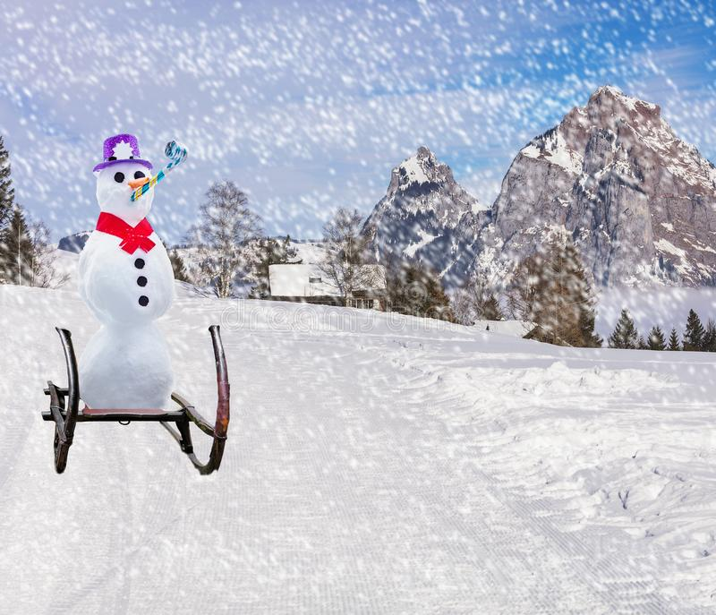 Merry christmas a funny party snowman sleighing down a ski hill slope on a sled in snowy weather stock photo