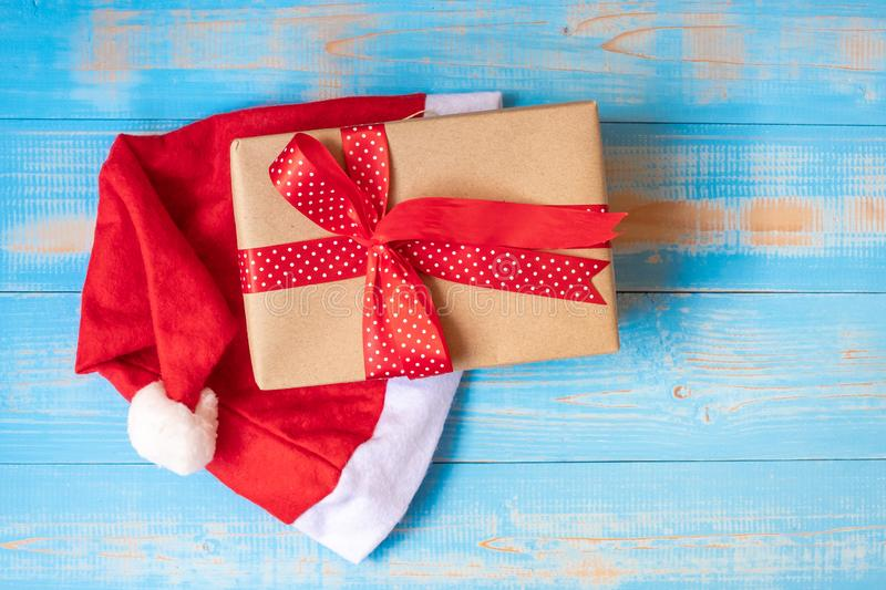 Merry Christmas gift box or Present with Santa Claus hat on blue wooden background stock photography
