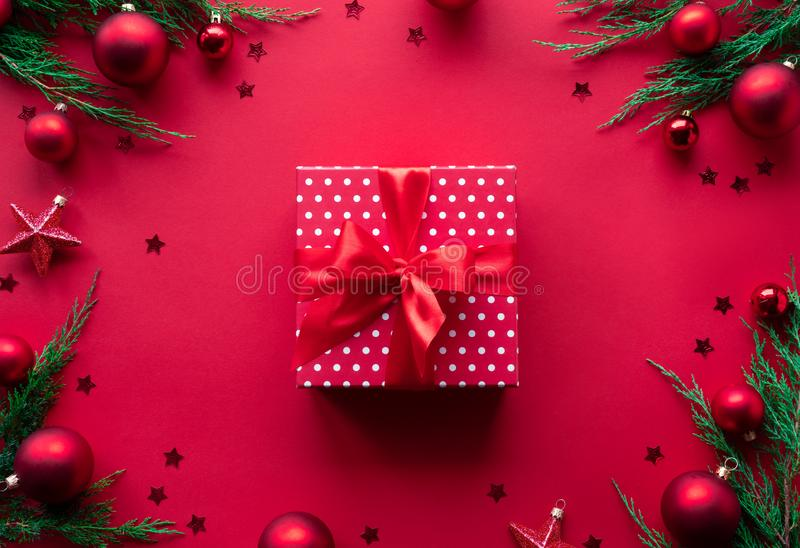 Merry Christmas gift box with ribbon bow on red background, flat lay royalty free stock image