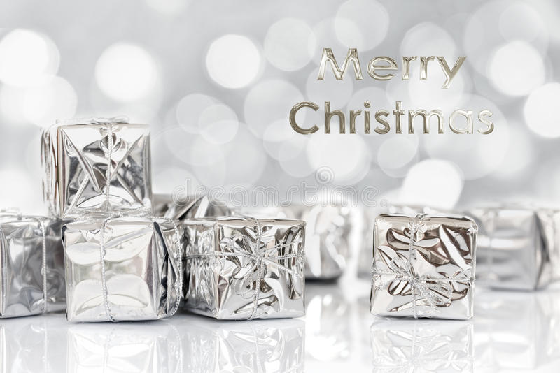 Merry Christmas gifts in shiny silver paper, bokeh background stock images