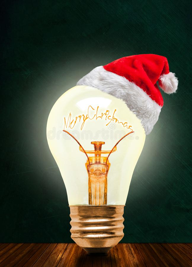Merry Christmas Glowing Light Bulb With Santa Hat And Copy Space. Glowing light bulb wearing Santa hat with Merry Christmas message on chalkboard background with royalty free stock photography
