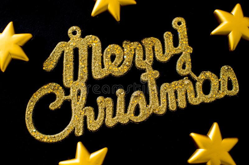 Merry Christmas golden text on a black background with stars stock photo